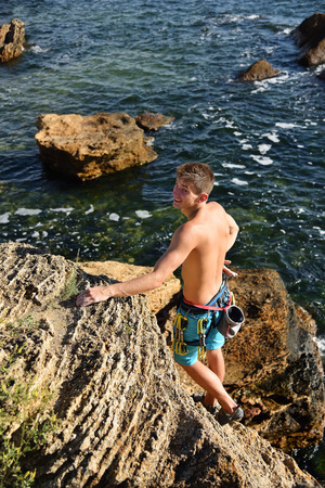 Young man climbing on a rock with sea on the background Stock Photo