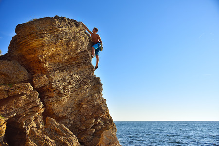 clambering: Young man climbing up on yellow mountain on ocean background
