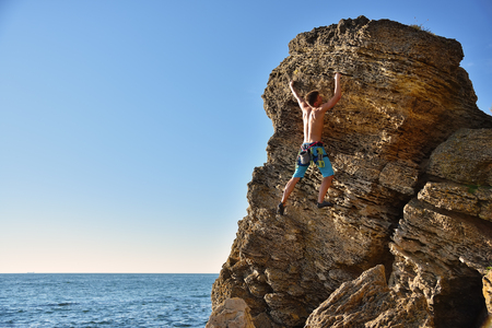rockclimber: Young man climbing up on yellow mountain on a sea background