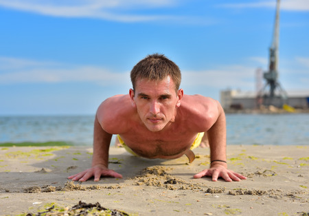Young yoga man in a dog pose on beach