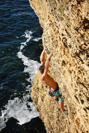 rockclimber: athletic man climbing on a rock, view from above