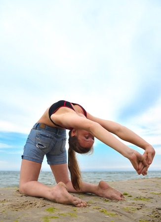 Young girl practicing yoga on a beautiful beach