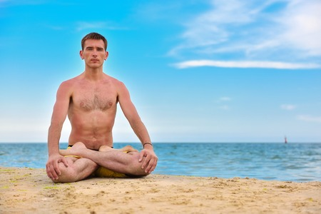 young man in meditation near the ocean. close up