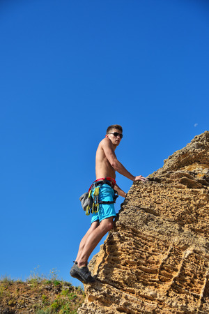 Rear view of young male climber climbing with carbines Stock Photo