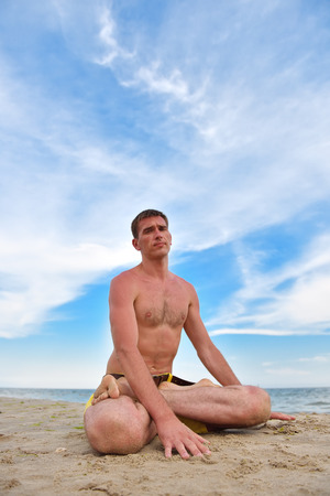 young man sitting in lotus position near the ocean. close up