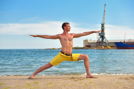 prana: man making yoga exercises on beach on harbor crane background
