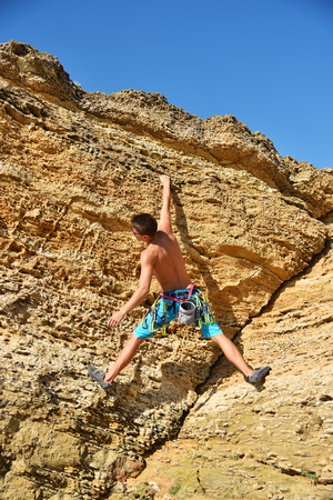 Young man climbing on a Mountain. clear cloudless sky