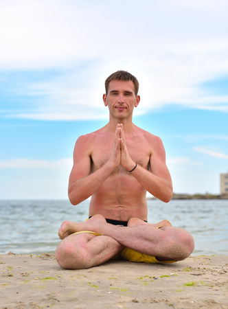 young man in lotus position and meditation near ocean. close up