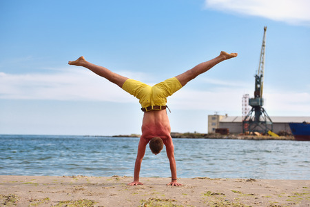 Young man practicing yoga on beach with beautiful blue sky