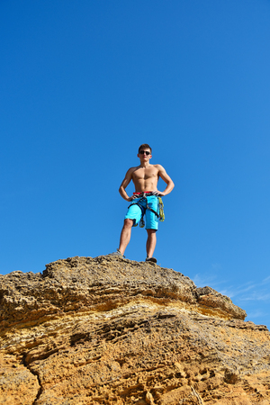 rockclimber: athletic climber man standing back on top mountain