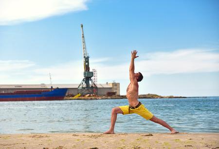 prana: man making yoga exercises on harbor crane background