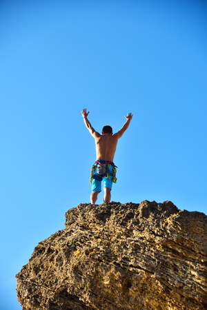 rockclimber: Extrime Climber Raising Hand On Top Of Mountain.  Concept Of Success