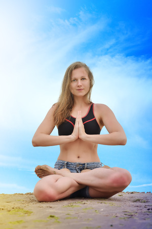 young woman in lotus position meditation on a sky background photo
