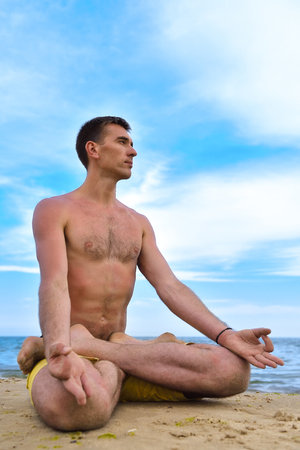 young man in lotus position and meditation near sea. close up