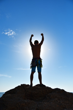 Extreme Climber Raising Hands On Top Of Mountain.  Concept Of Success