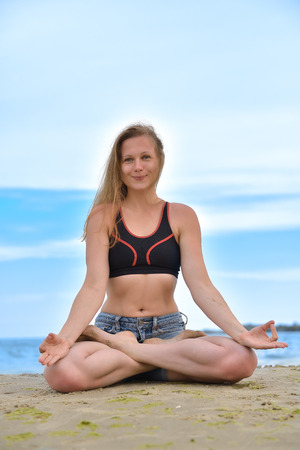 young girl in lotus position meditation near the sea photo