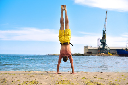 man doing yoga standing on hands. industrial harbor crane background Stock Photo