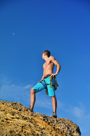 athletic climber man standing back on top mountain