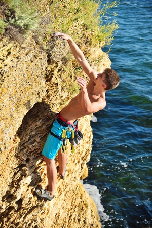 Young male climber hanging by a cliff on a sea background