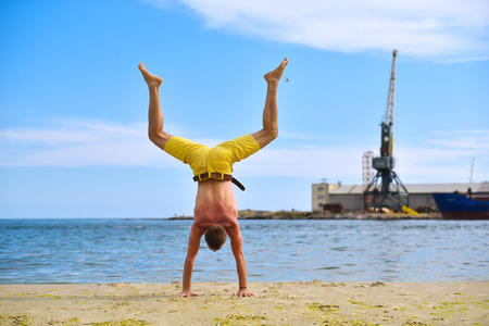 yoga man standing on hands and does the splits photo