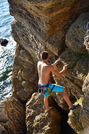 clambering: male rock climber climbs on rocky wall, view from above Stock Photo