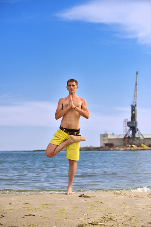 Young man practicing yoga on beach with beautiful blue sky photo