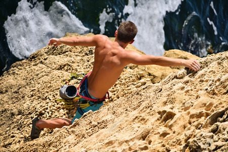extreme climber man caught on a rock, view from above Stock Photo