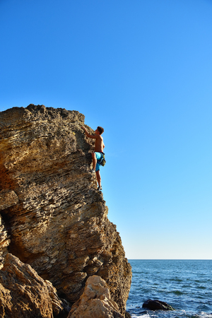 Young man climbing up on yellow mountain on ocean background