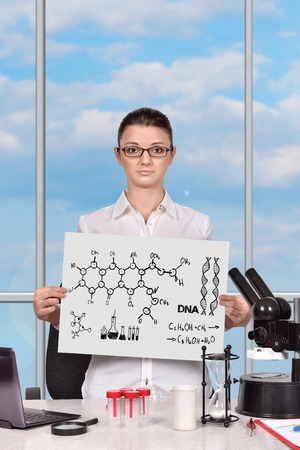 scientific woman in laboratory and holding clipboard with chemical symbol photo