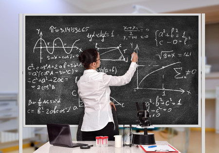 teacher in laboratory drawing formula on chalkboard photo