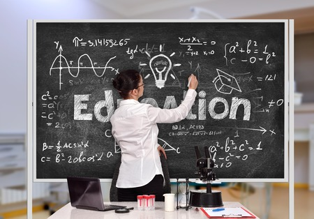 caucasian teacher woman in laboratory drawing formula on black board photo