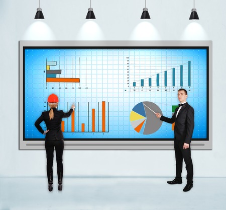 businesspeople pointing to tv screen with stock chart photo