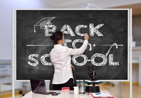 female teacher drawing back to school on blackboard in classroom photo