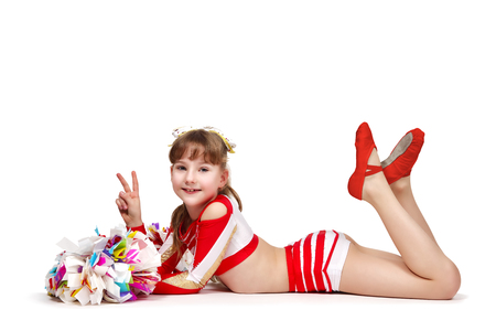Young cheerleading girl with pompoms lying on the floor and showing victory symbol