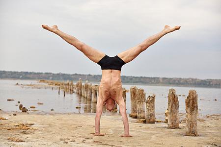 Yogamann, der auf Händen steht und die Spaltungen tut