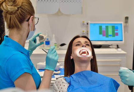 Dentist Looking On Jaw Cast. Patient With Braces In Dental Office Stock Photo