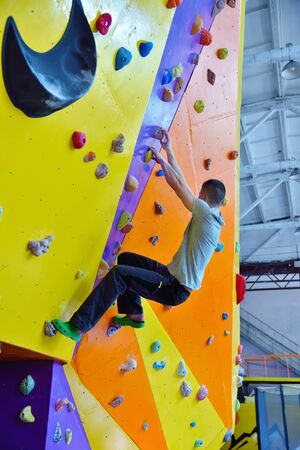 Young man climbing up on practice wall in gym. Extreme and healthy lifestyle concept.