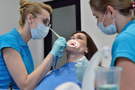 Woman Dentist And Assistant Examine Patient With Braces In Dental Office. Dental Health Care Concept