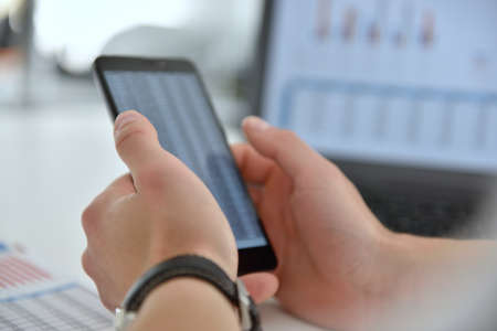 Accountant checks business report on cellphone. 스톡 콘텐츠
