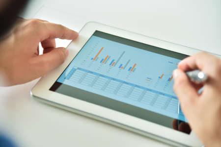 Top view of hand using digital tablet computer with financial data. Business and management concept. Close up