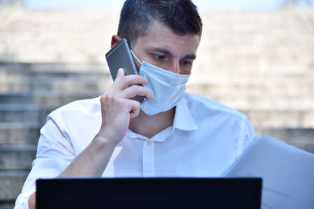 Young businessman in mask working outdoor and speaks on phone. Pandemia covid concept