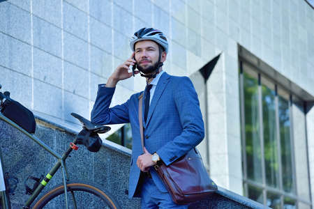 Bearded businessman talking by mobile phone with bicycle. Business and environmental of transport concept Stok Fotoğraf