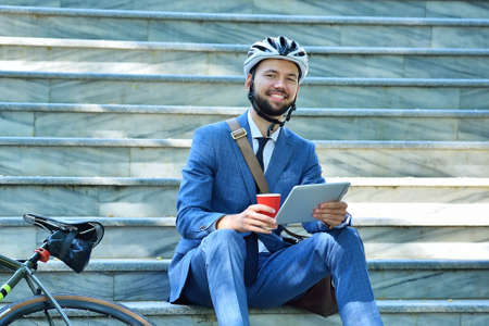 Businessman with bicycle sitting on stairs and using digital tablet. Business and alternative transport concept Stok Fotoğraf