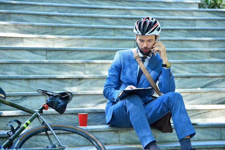Businessman  sitting on stairs analyzes report and talking on phone with bicycle. Business and urban style concept