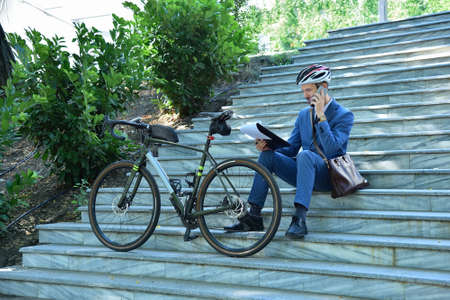 Businessman analyzes business report and talking on mobile phone with bike. Business and urban style concept