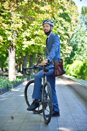 Bearded businessman in helmet with bike. Business and urban style concept. Close up Stok Fotoğraf