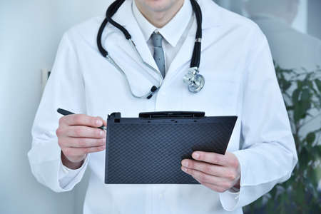 Doctor holding black clipboard. Healthcare and medicine concept.