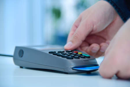 Hand makes payment by blue credit card and enters pin code on keyboard. Electronic money and shopping concept. Close up