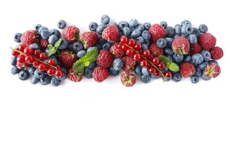 Various fresh summer berries on white background. Ripe raspberries, blueberries, and red currants, mint. Berries at border of image with copy space for text. Background berries. Top view.