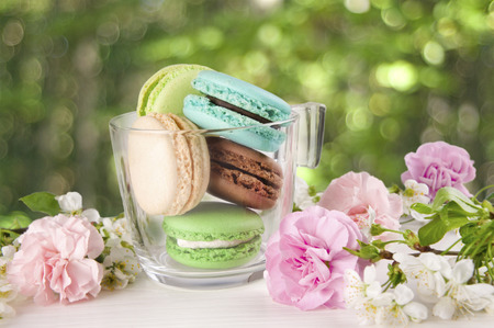 French macaroons in cup. Turquoise, chocolate and green macaroons with spring flowers. Spring concept. Stock Photo